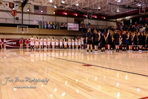 The teams line up for the National Anthem prior to the start of the game. The Plainville Lady Cardinals defeated the Hoisington Lady Cardinals by a score of 49 to 35 at the Hoisington Activity Center in Hoisington, Kansas on February 5, 2019. (Photo: Joey Bahr, www.joeybahr.com)