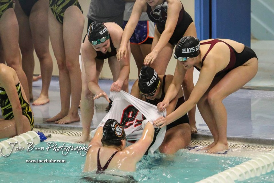 Teammates from Hays transfer a football jersey in the post meet T-Shirt Relay. The Great Bend Girls Swimming Invitational was held at the Kirkman Activity Center on the campus of Barton Community College in Great Bend on 4 20190426, 2019. (Photo: Joey Bahr, www.joeybahr.com)