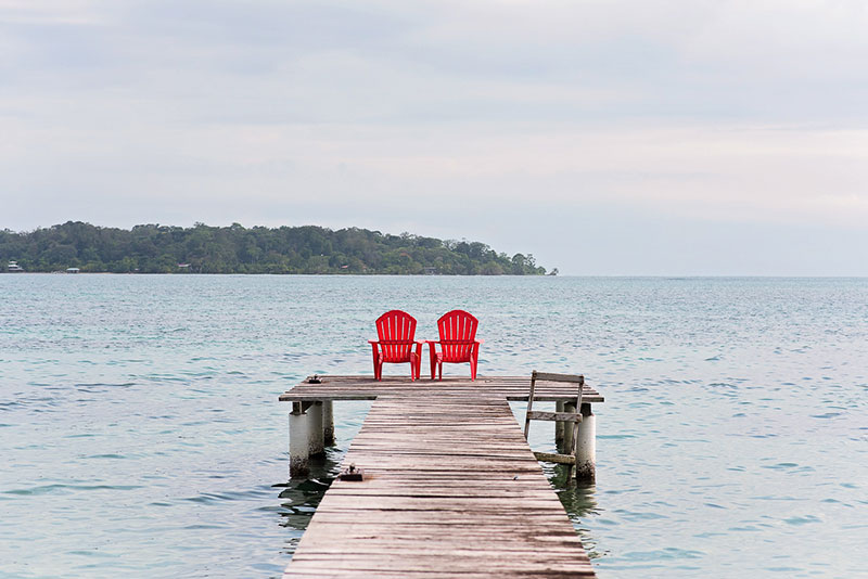 A Dock, Two Red Chairs, and a Wide Open Ocean