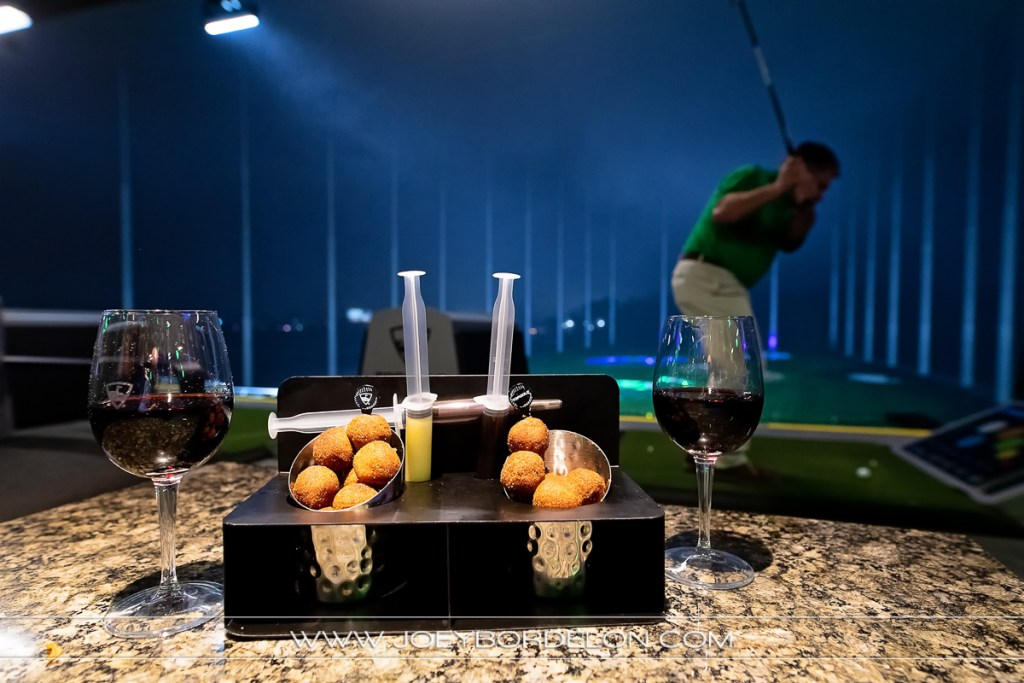 Top Golf signature donut holes and wine in forefront; man golfing in background