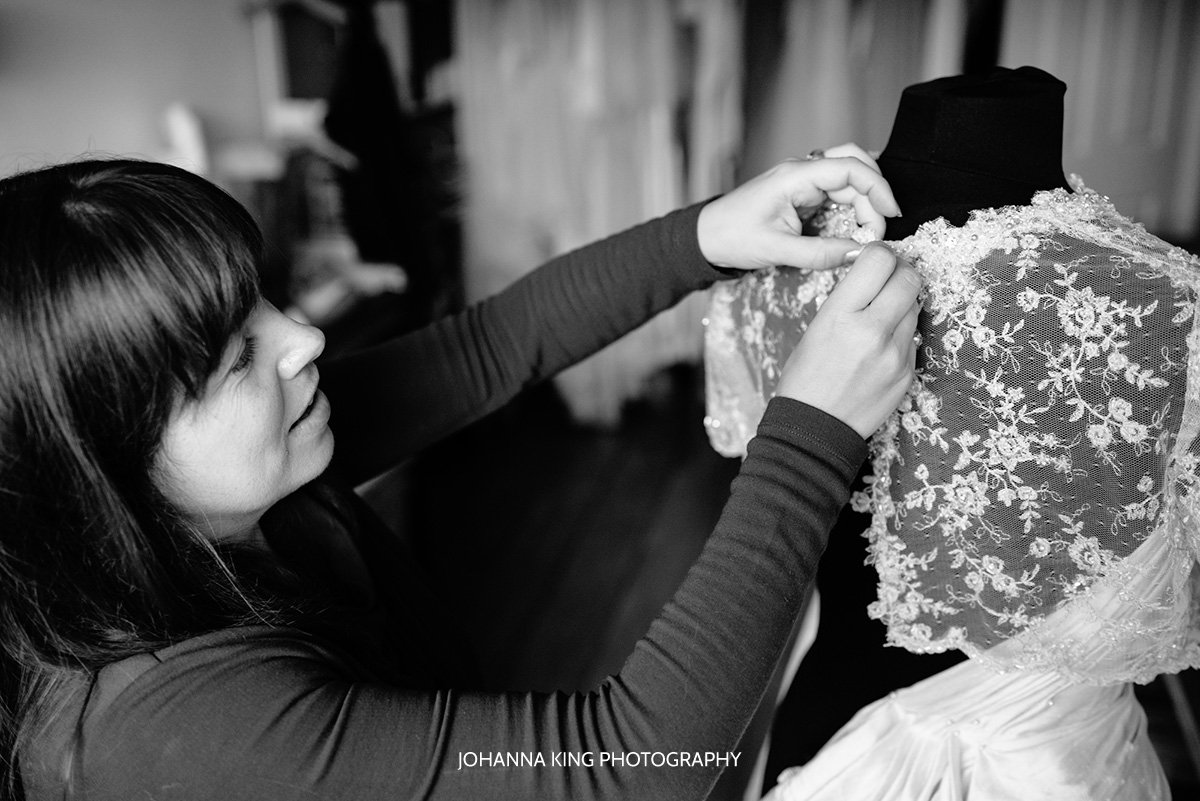 Sarah smiling and closing the button of her bridal twinkle bolero