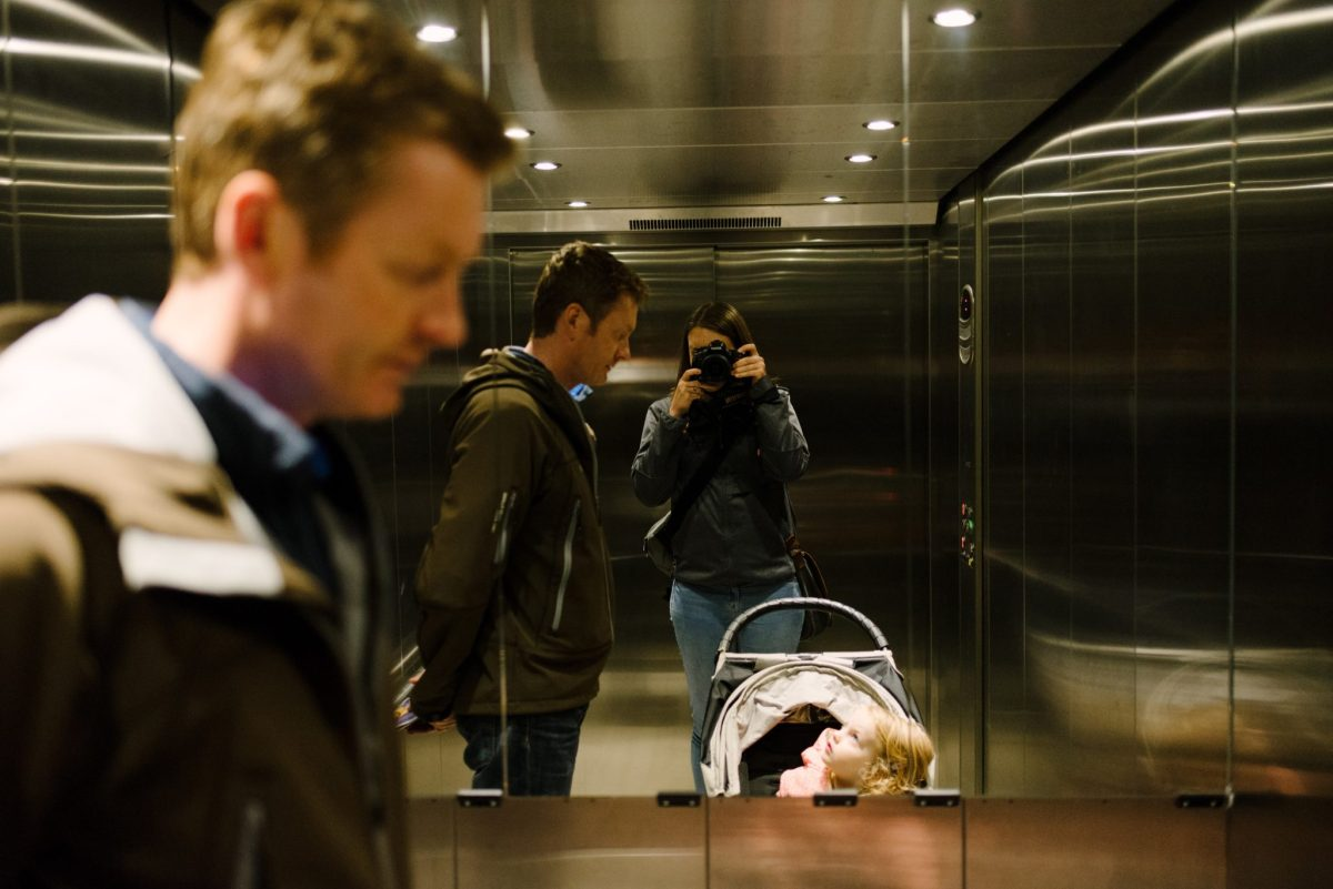 A mirror selfie of a mum in a lift with her husband and daughter. 2nd of 8 Ways for mums to exist in family photos