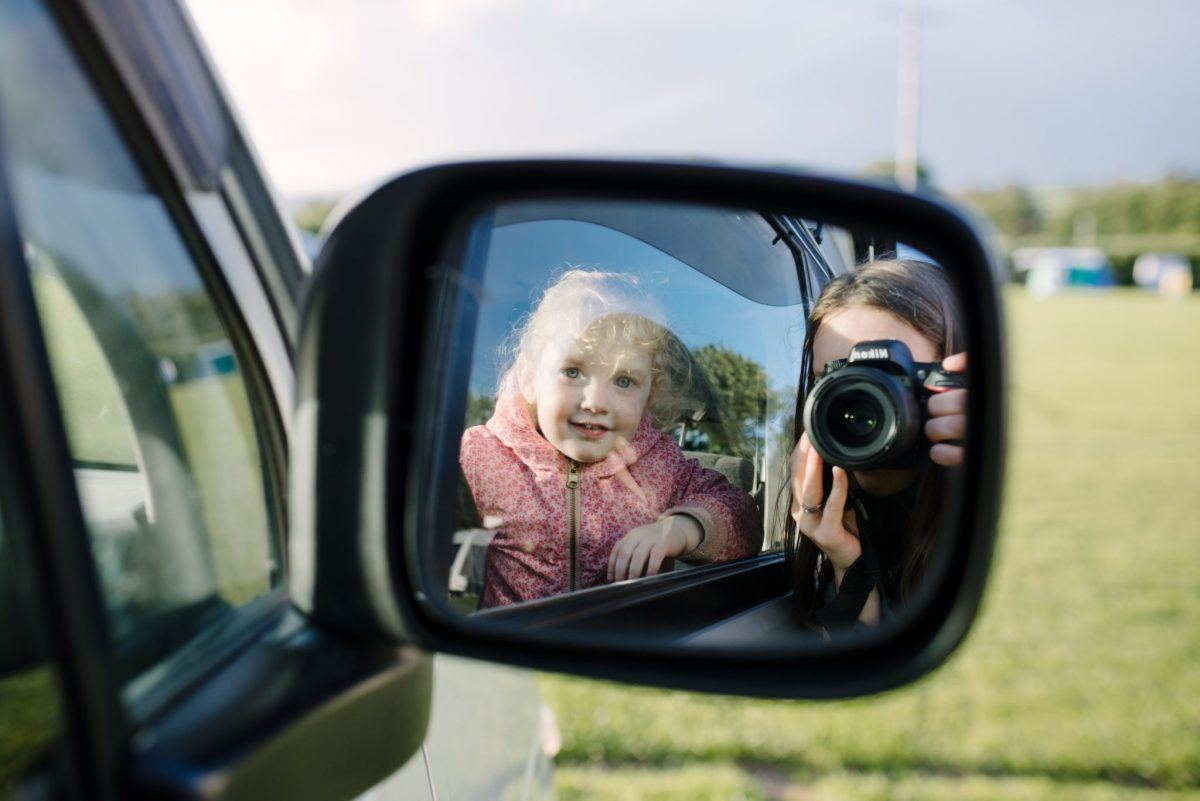 A mirror selfie of a mum with her daughter in a car side mirror. 2nd of 8 Ways for mums to exist in family photos