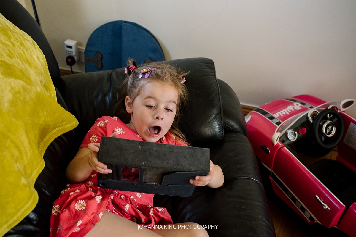 Réiltín's big sister watching her tablet while her parents administer chemo to Réiltín