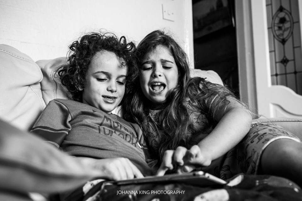 Siblings playing and fighting over a game on the tablet