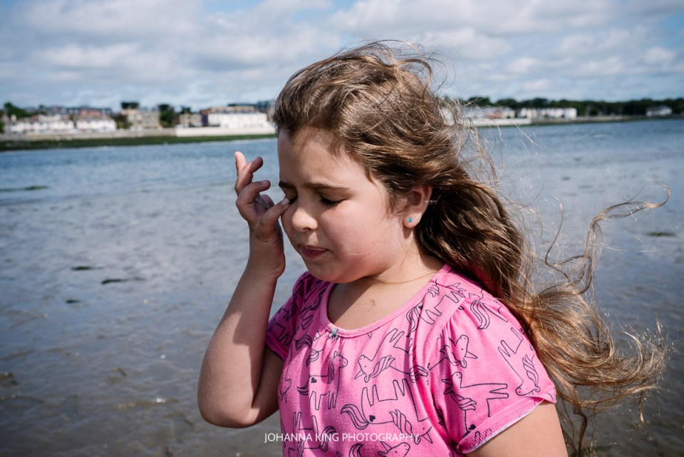 Daughter with long hair wipes her eye from splashed water.