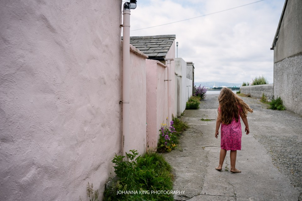 A quiet moment of a girl walking back to the house with the pink wall.