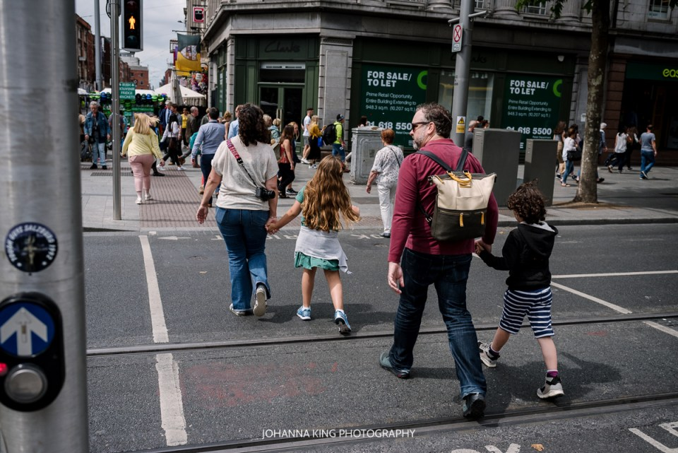 Family crossing O'Connell Street in Dublin City Centre on their vacation