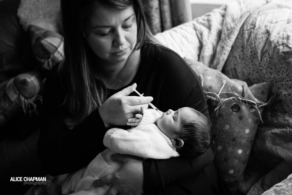 Mother giving a medicine to her newborn baby at home - Documentary Newborn Photography Example