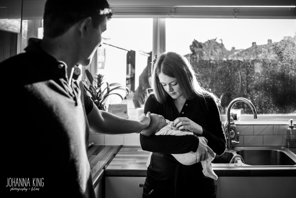 Mother holding and looking at her newborn baby in her kitchen and  father rubbing the baby's head softly - Documentary Newborn Photography Example