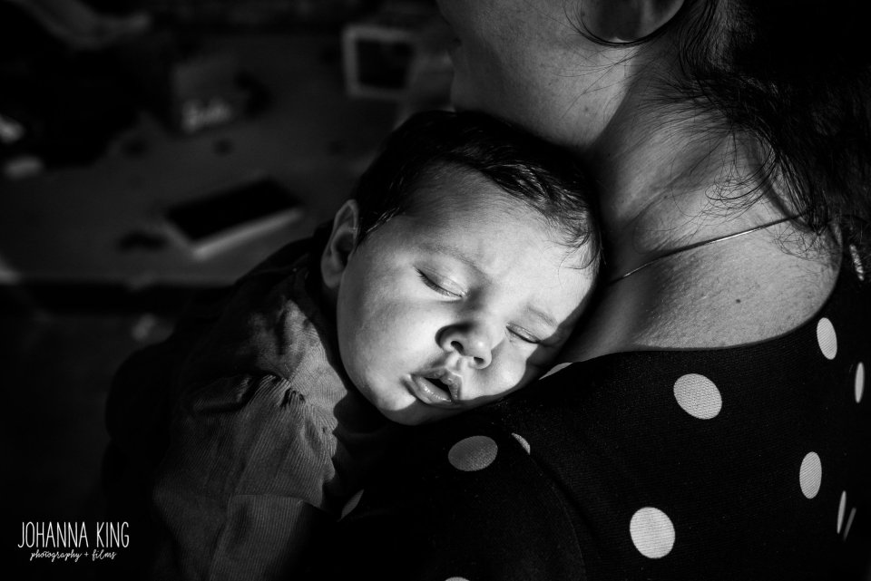Baby asleep on her mother's shoulder while the winter light highlights her features - Documentary Newborn Photography Example
