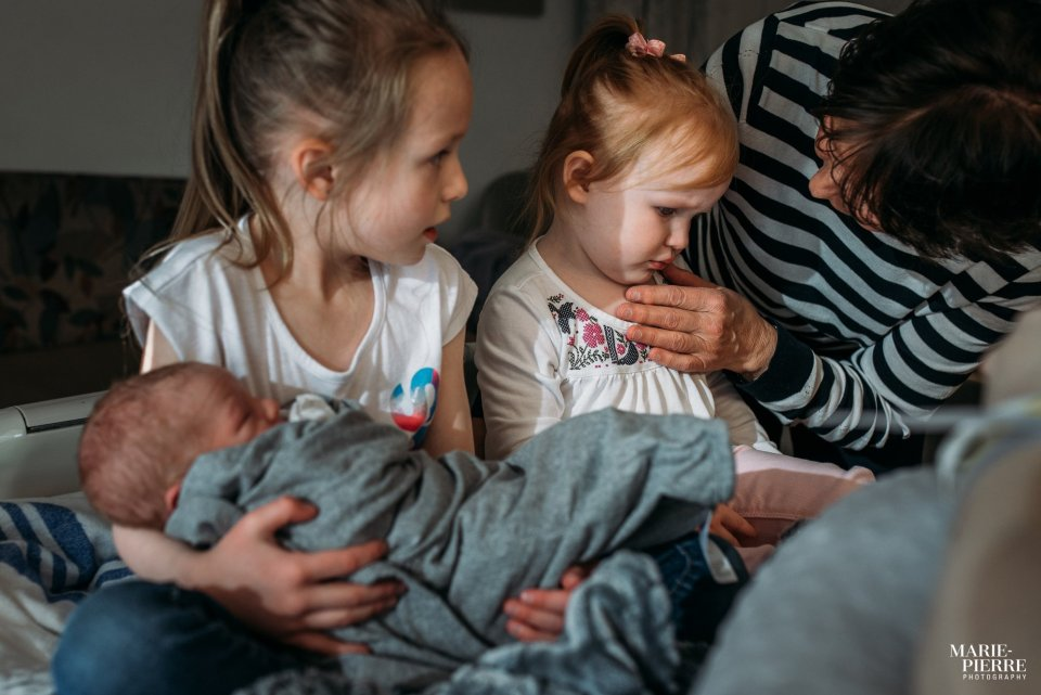 Two older sisters meet the new baby for the first time in hospital and want to hold the baby - Documentary Newborn Photography Example