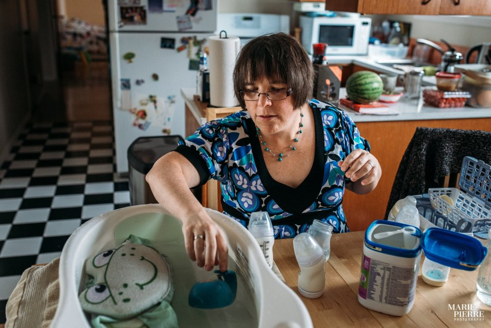 Mother preparing the bath and bottles for her newborn baby in her kitchen - Documentary Newborn Photography Example