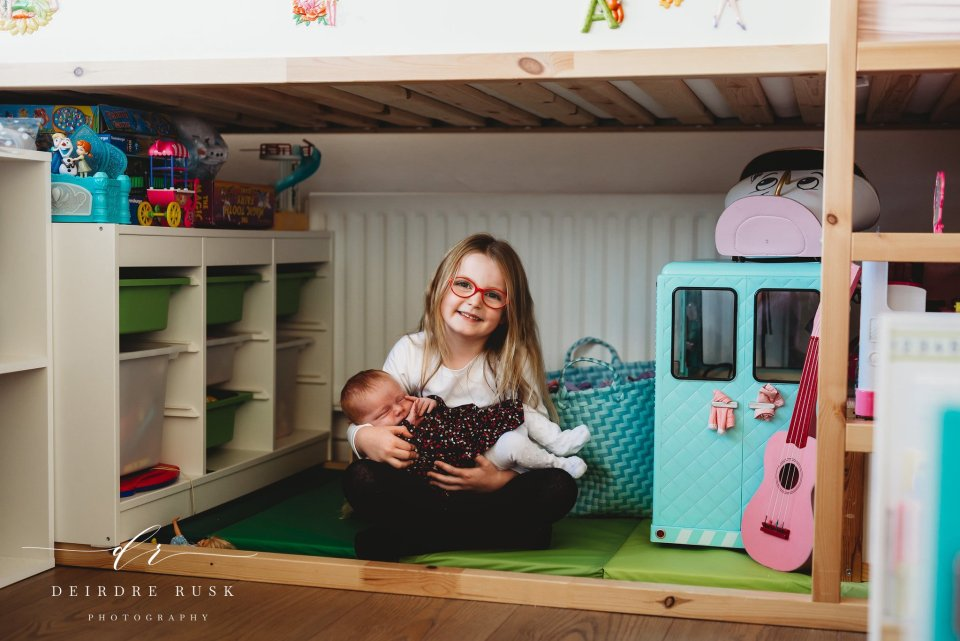 Big sister holding her baby sister under her big girl's bed in the middle of her toys - Lifestyle Newborn Photography Example