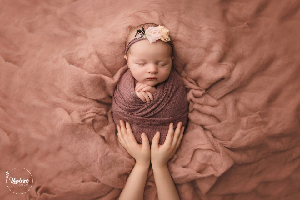 Sleeping swaddled newborn baby wearing a flower headband with sibling's two hands cupped around the legs - Posed Newborn Photography Example