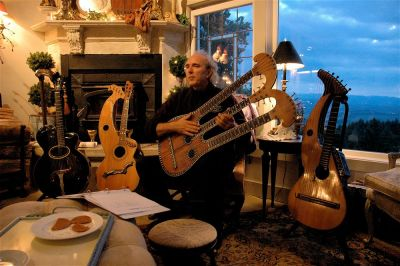 John Doan home concert with various antique harp guitars with the sun setting in the background through the window.