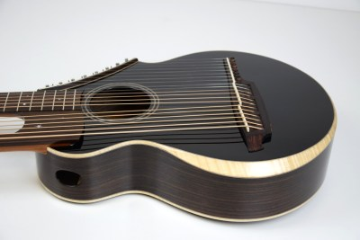 Brunner Harp Guitar from Bass side featuring curly Maple binding with beveled arm rest