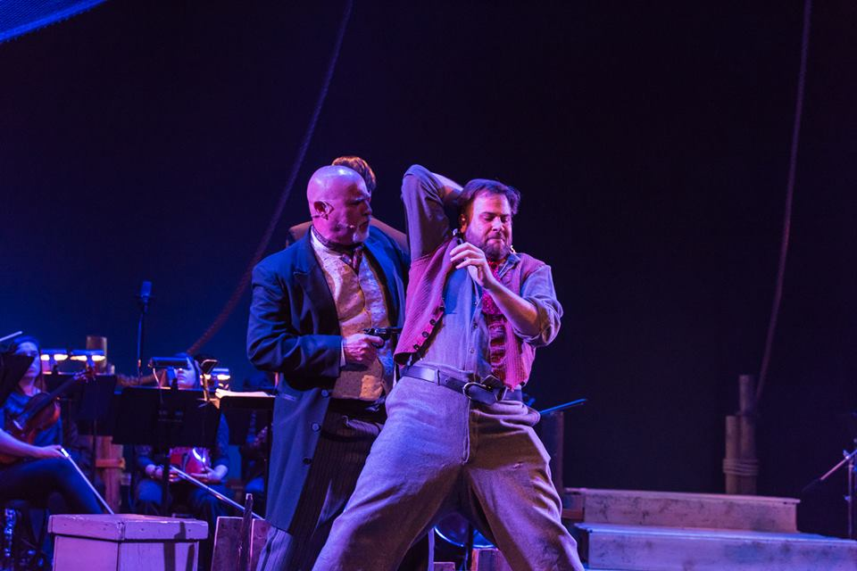 John George Campbell as David Bascombe, in CAROUSEL in CONCERT, telling Jigger, played by James C. Mulligan, to drop the knife.