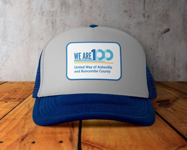 A blue and grey trucker hat with a patch on it with the Next 100 United Way logo on the front.