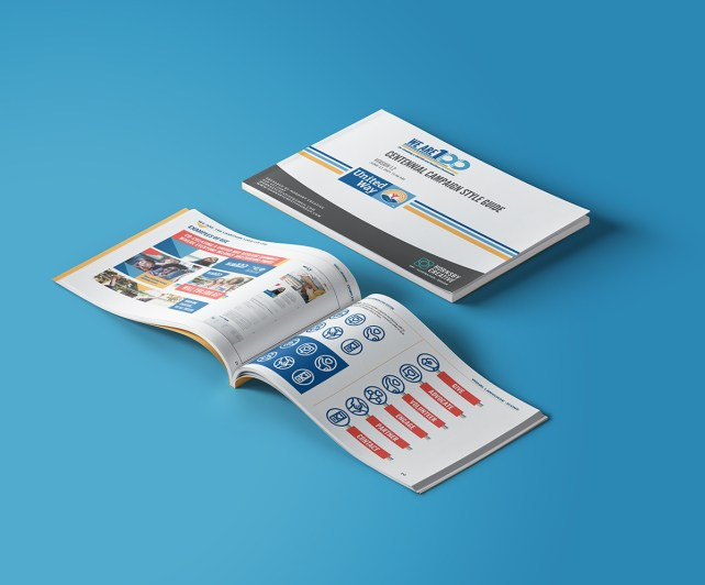 Photo of a brand guide for United Way laying open on a blue background with a closed version above.