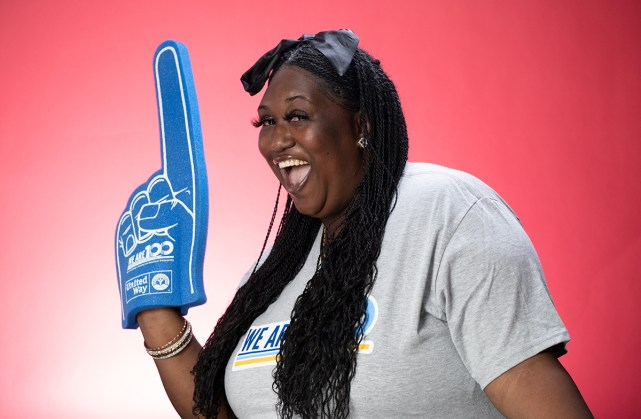 A black womand with long hair and a big smile is wearing a blue foam finger with the We are 100 logo on it.