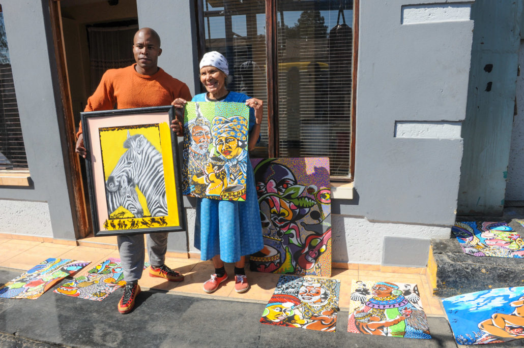 Tumi Masite, left, is an artist who participates in the Maboneng Township Arts Experience, an initiative that invites outsiders inside the homes of artists who showcase their works there. He and his grandmother show off some of his paintings.