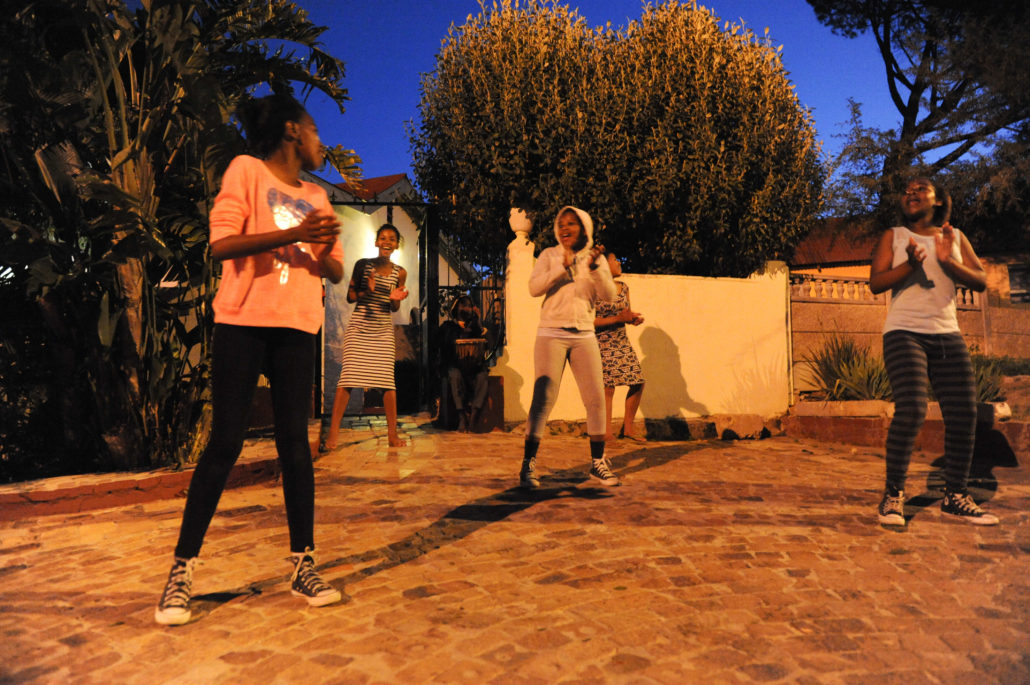 A group of girls welcome us to the township of Kayamandi with a song a dance