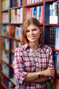 Portrait of young attractive salesperson in own small book shop