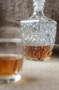 Carafe and glass of whisky, whiskey bourbon on a burlap, sacks background