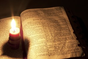 Single candle flame illuminatied pages from the Book of Psalm in an old bible.
