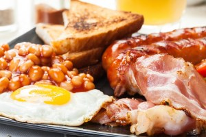 Full English breakfast with bacon, sausage, fried egg, baked beans, toast