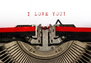 Old typewriter with sample text I LOVE YOU! Red words on white paper