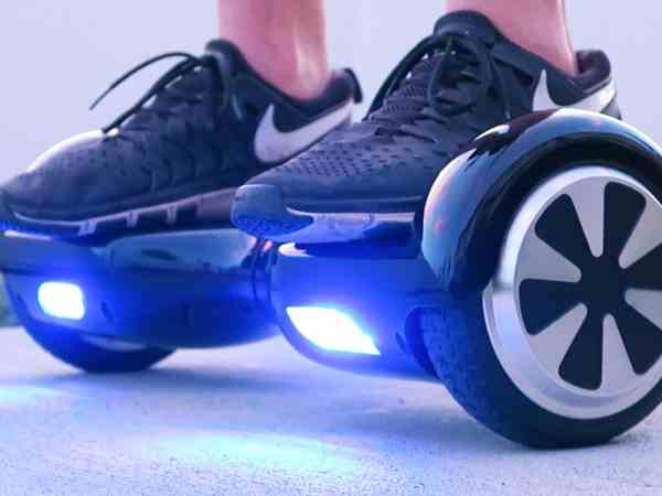 blue hoverboard with black nike shoes on it