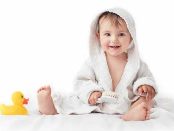 Little baby smiling under a white towel, bath time