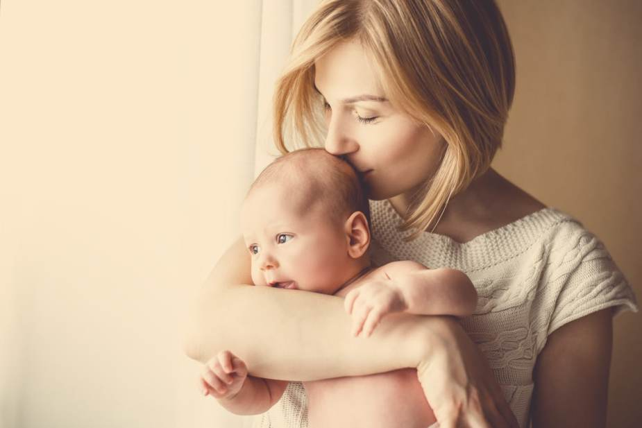 Newborn baby in a tender embrace of mother at the window.
