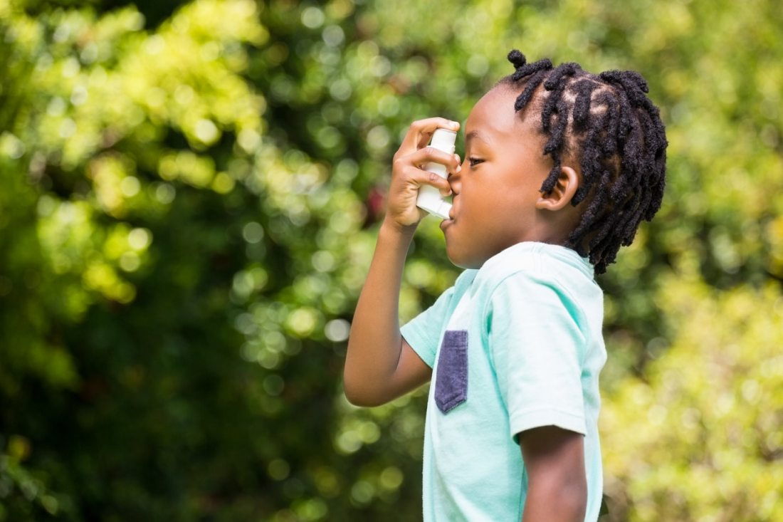 young black child using inhaler outside