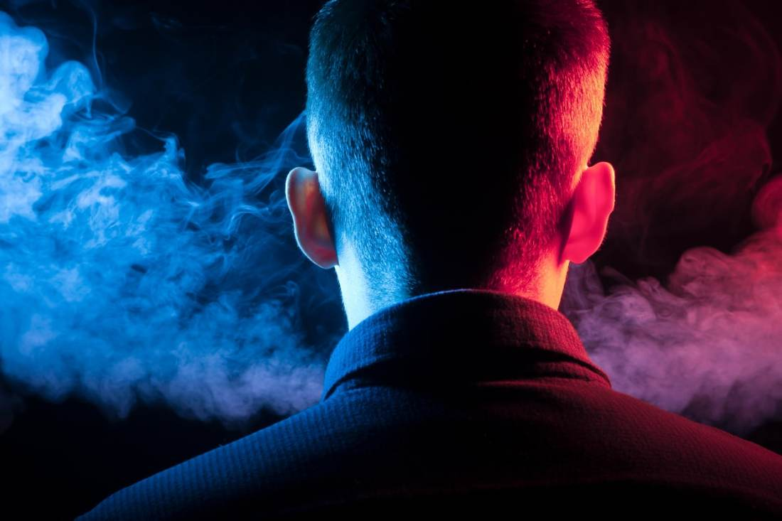 backside of a male with short hair, in the dark with what appears to be vapor in front of him; red and blue lights on either side of head