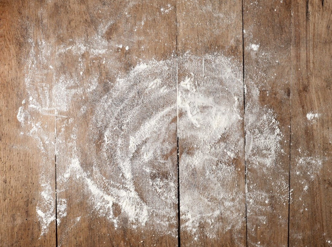 image of flour that appears to have been strewn about a wood tabletop