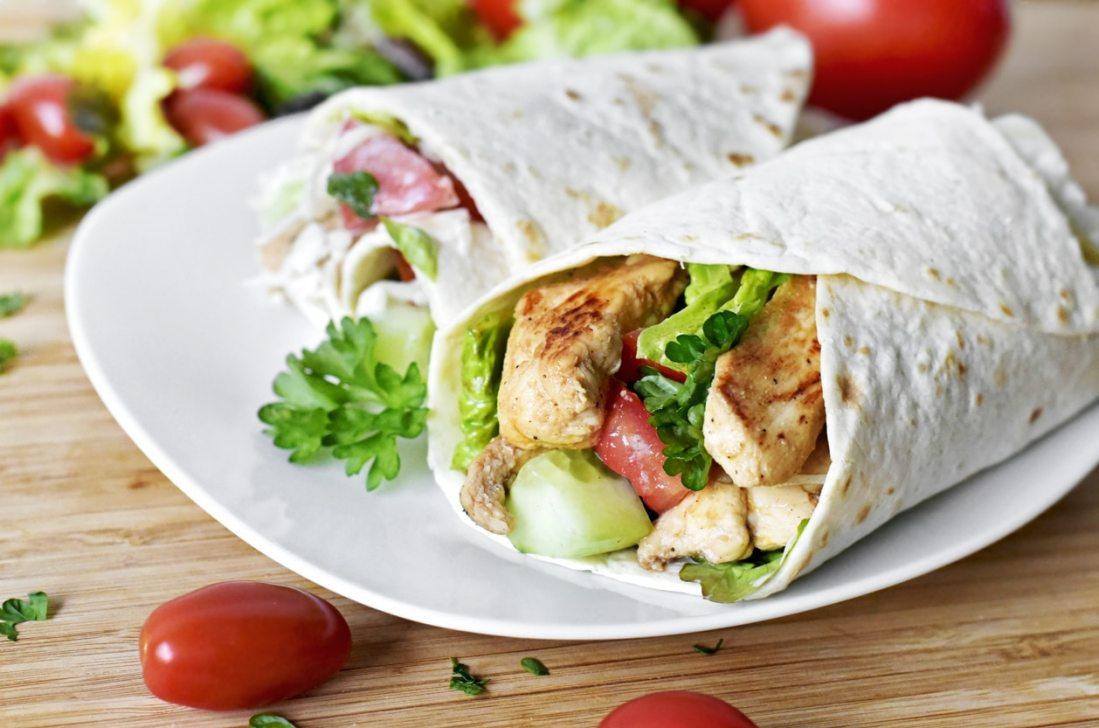 chicken wraps on a white plate with garnish surrounding it