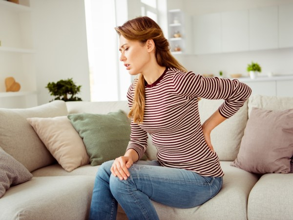 young woman sitting on living room couch in back pain