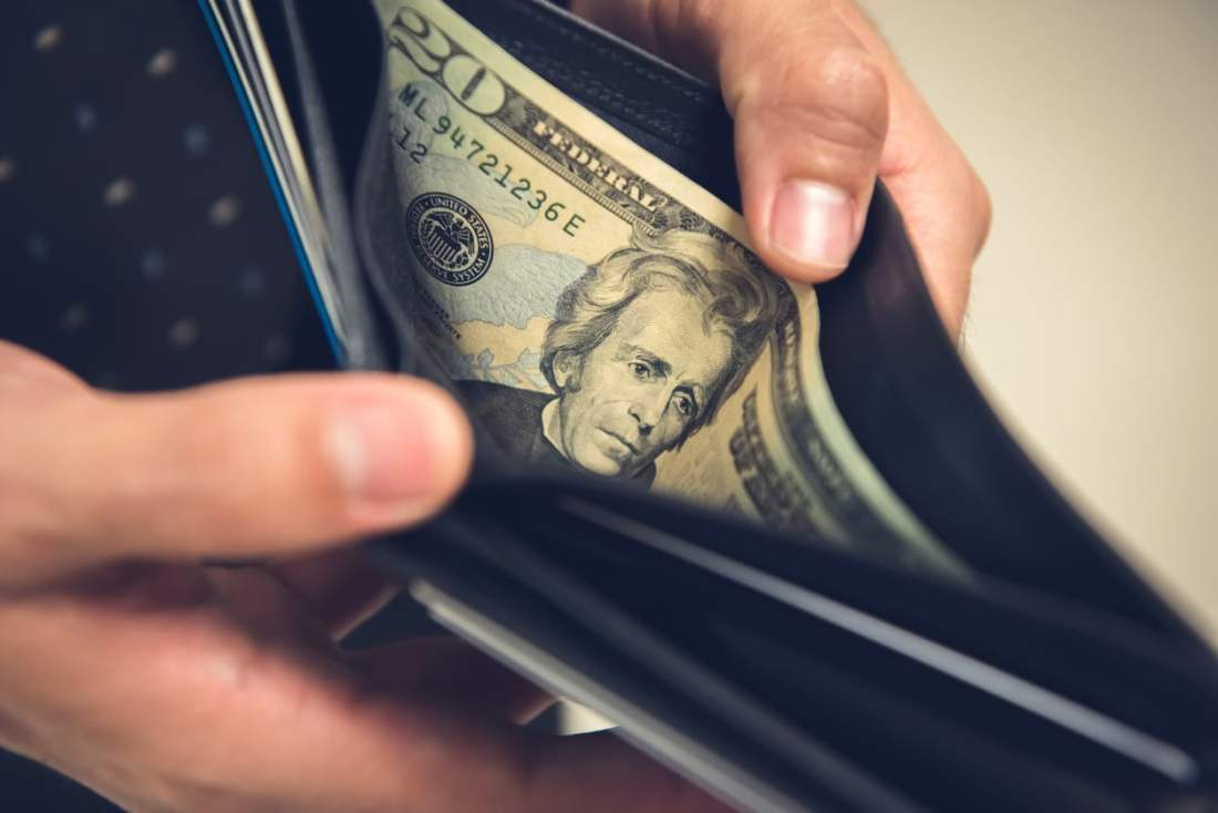 image of hands holding open a wallet with only a twenty dollar bill in it