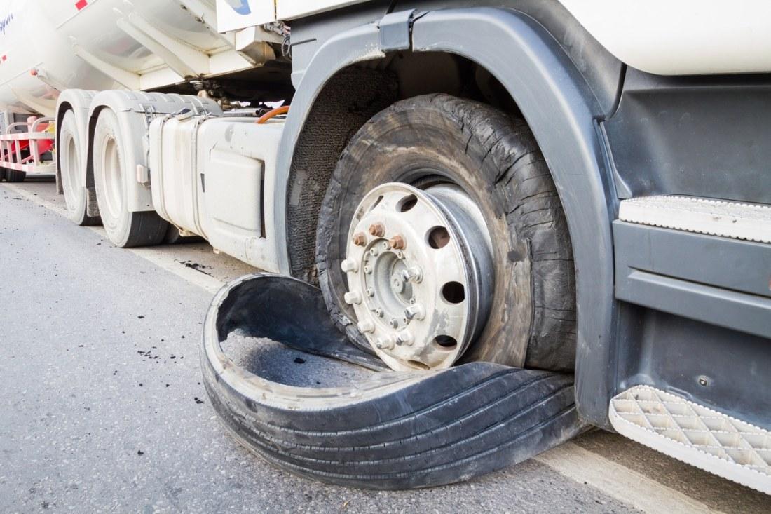 closeup of defective, damaged 18 wheeler semi truck burst tires by highway street