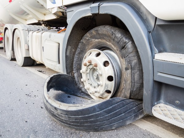 closeup of defective, damaged 18 wheeler semi truck burst tires by highway street