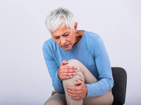 older woman grasping her knee in pain while sitting