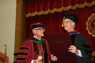Weeks on being granted an honorary doctor of laws (L.L.D.) by the trustees of National University of Health Sciences, with James Winterstein, president, pictured.
