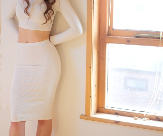Teen girl posed in front of window wearing white body con outfit