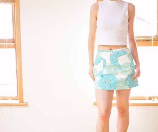 Teen girl wearing aqua coloured 60s patterned skirt from Top Shop