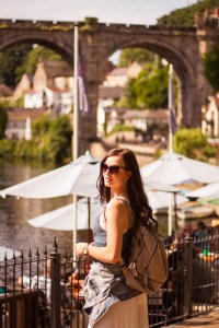 Young woman wearing backpack in front of bridge over river in Yorkshire UK