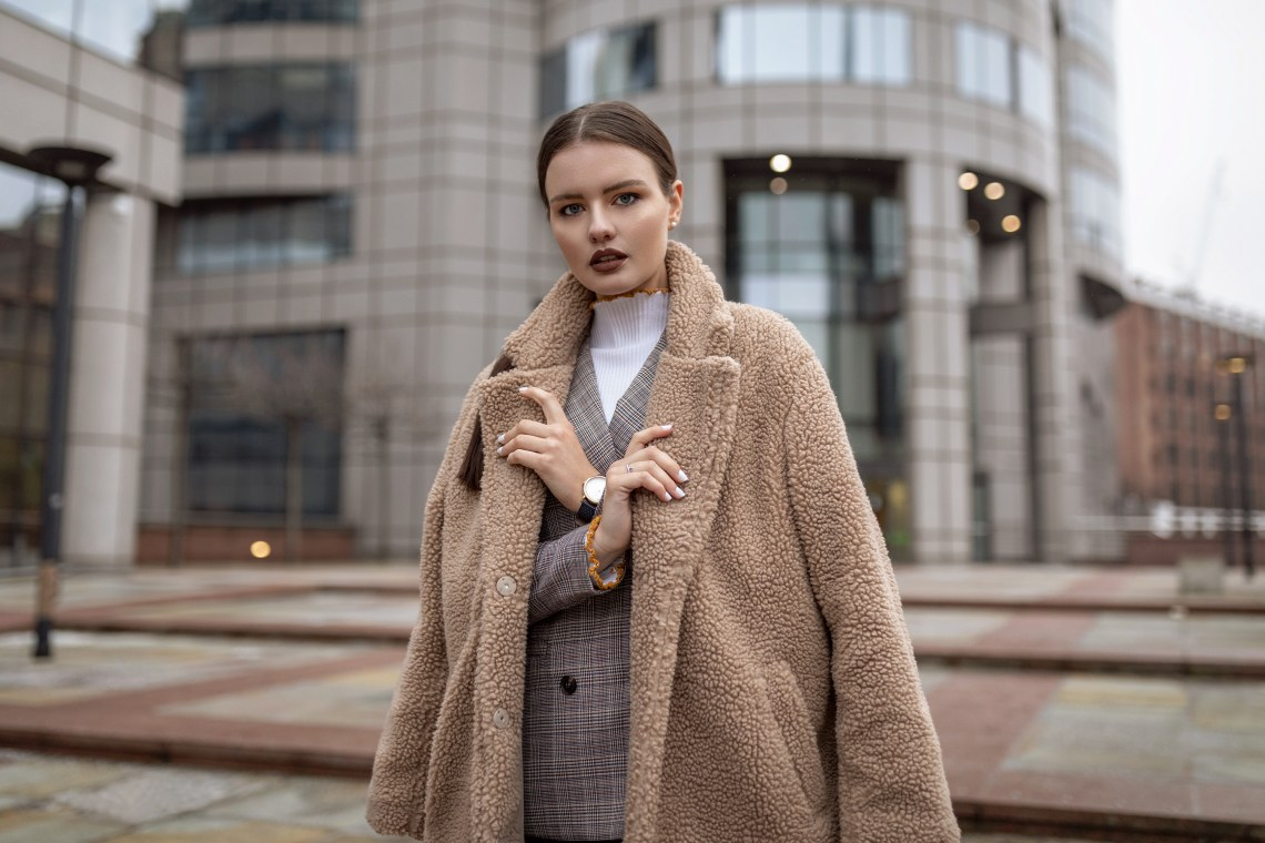 Young woman wearing beige teddy bear coat