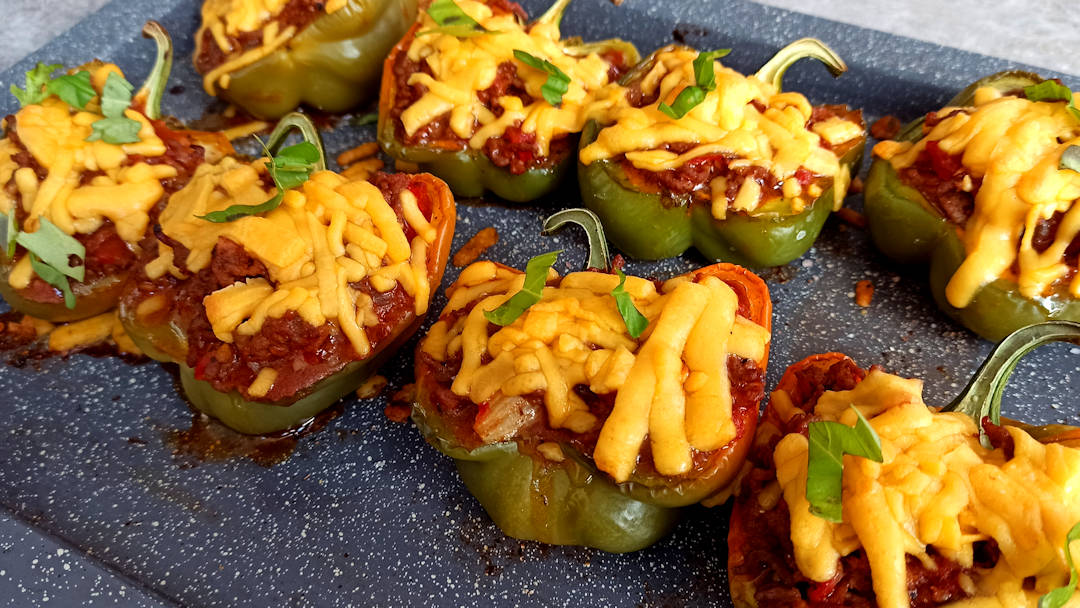 Hacher quelques de feuilles de basilic et décorer les poivrons farcis au bœuf tomates et cheddar